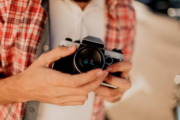 Centrarse en la cámara. detalles hombre sujetando la cámara de cine, haciendo fotos