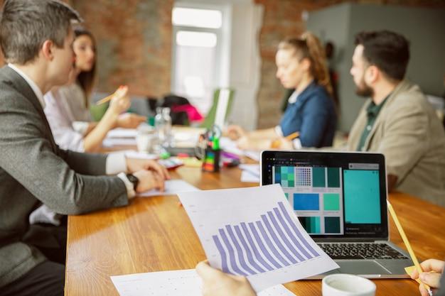 Centrarse en la computadora portátil. grupo de jóvenes empresarios que tienen una reunión. grupo diverso de compañeros de trabajo discuten nuevas decisiones, planes, resultados, estrategia. creatividad, lugar de trabajo, negocios, finanzas, trabajo en equipo.