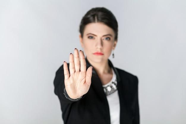 Centrarse en la mano. en serio, mujer mostrando señal de parada con la mano. foto de estudio, interior. aislado sobre fondo gris