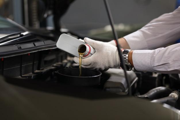 Centrarse en manos especializadas masculinas sosteniendo el bote de maquinaria líquida