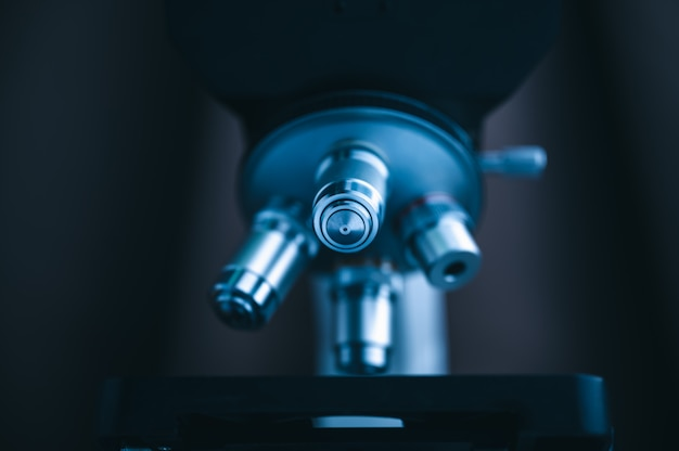 Centrarse en el microscopio con lente de metal para experimentos.