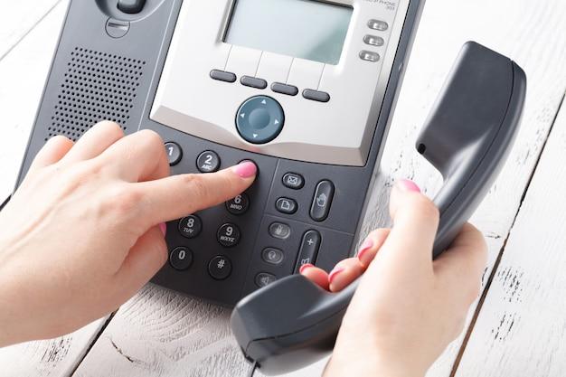 Centro de atención telefónica o concepto de teléfono de oficina, número de prensa de dedo femenino en el teclado