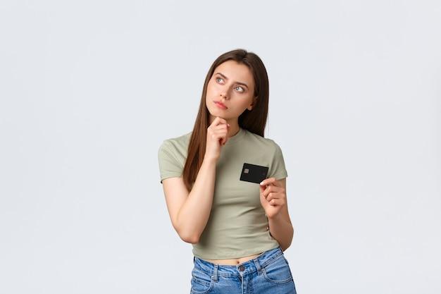 Centro comercial, estilo de vida y concepto de moda. mujer contenta pensativa pensando qué comprar por dinero