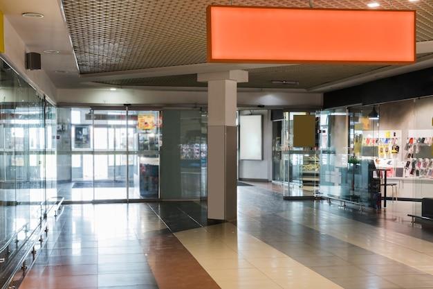 Centro comercial interior con signo naranja.