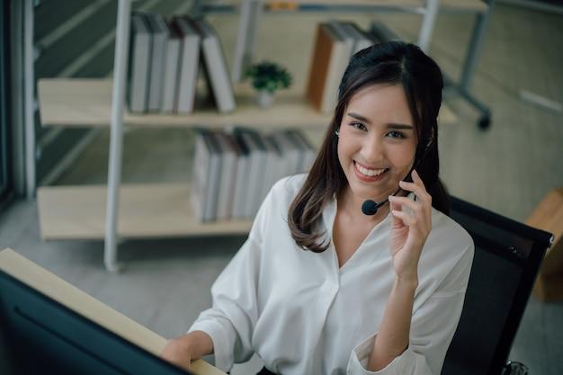 El centro de llamadas femenino feliz joven está sonriendo y mirando a la cámara.