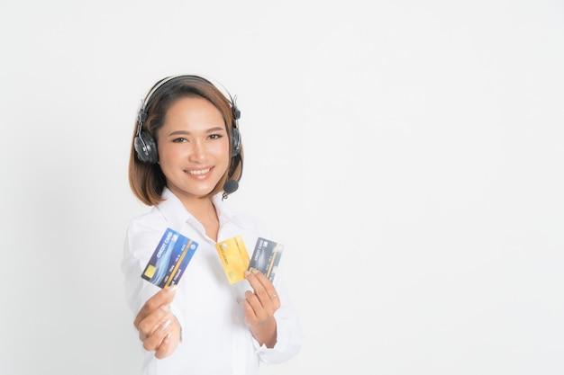 Centro de llamadas de mujer con auriculares y tarjeta de crédito.