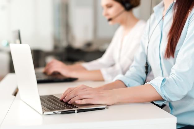 Centro de llamadas con trabajadores de oficina escribiendo en una computadora portátil y respondiendo a una llamada del cliente