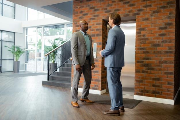 En centro de negocios. prósperos empresarios maduros vestidos de traje esperando el ascensor en el centro de negocios