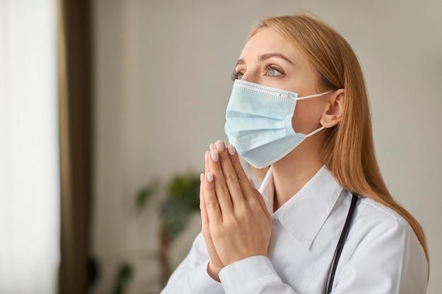 Centro de recuperación de covid doctora con estetoscopio y máscara médica rezando