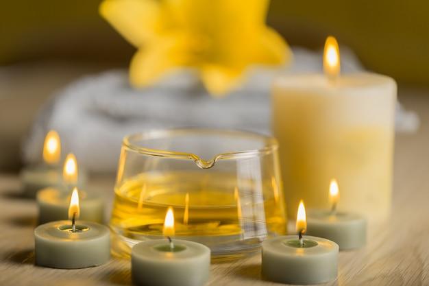 Centro de spa con aceite de hierbas, velas de spa y toalla.