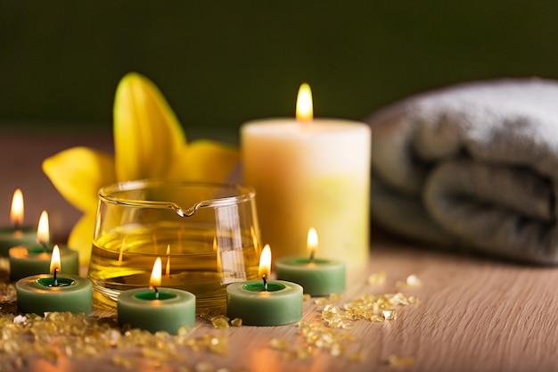 Centro de spa con aceite de hierbas, velas y toallas.