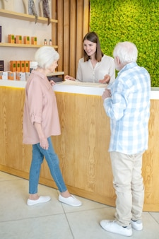 En centro de spa. pareja de ancianos discutiendo los procedimientos con un especialista en un centro de spa
