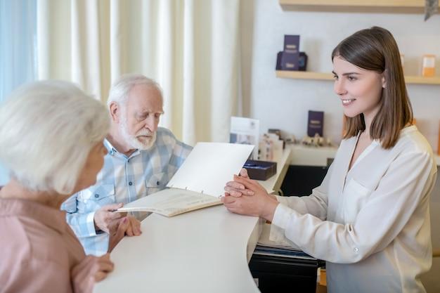 En centro de spa. pareja de ancianos eligiendo procedimientos con un especialista en un centro de spa