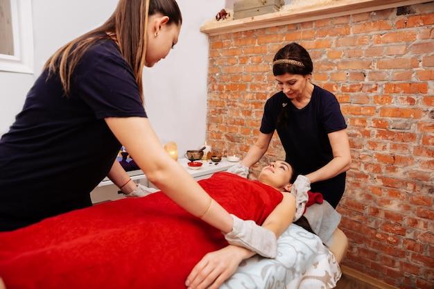 Centro spa profesional. los trabajadores profesionales del salón de spa tocar al cliente con guantes mientras ella está acostada en la cama