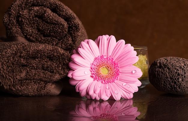 Centro de spa con toallas y flor de gerbera.