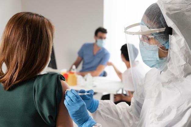 Centro de vacunación con médico sosteniendo una jeringa