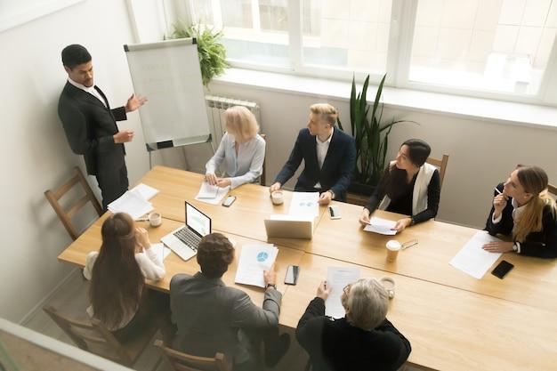 Ceo afroamericano dando presentación en concepto de reunión de equipo corporativo
