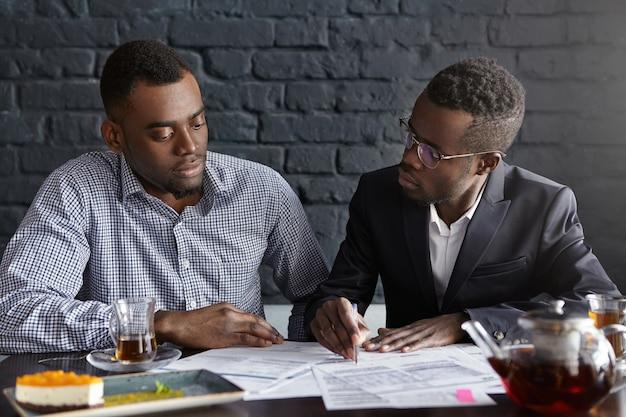 Ceo en elegante traje y gafas apuntando con bolígrafo a los papeles en la mesa frente a él