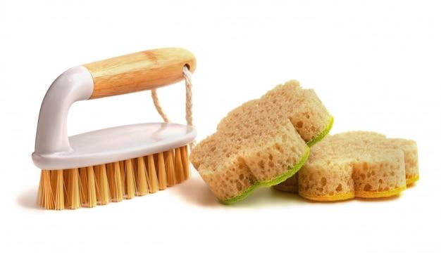 Cepille con un mango de madera y una esponja en forma de flor sobre un blanco aislado