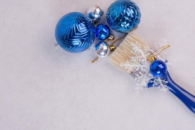 Cepillo azul con bolas de navidad sobre superficie blanca