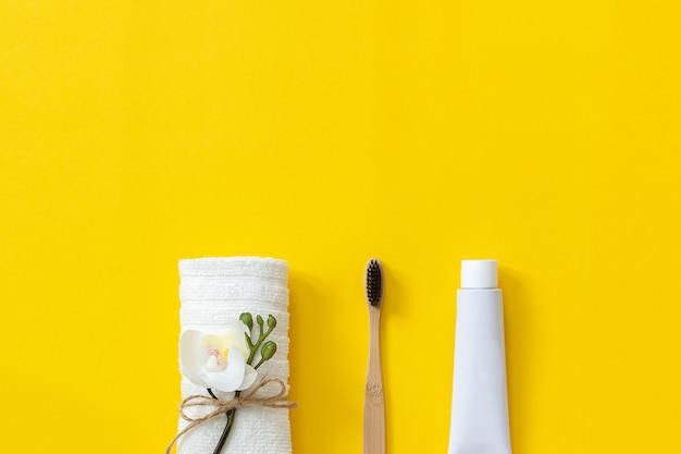 Cepillo de bambú ecológico natural, toalla blanca y tubo de pasta de dientes.