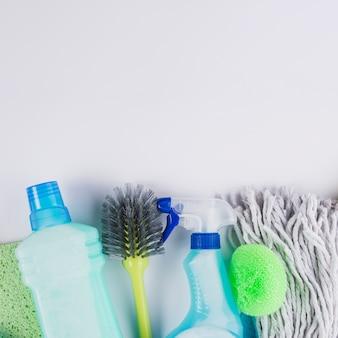 Cepillo de botellas de plástico, cabeza de la fregona y esponja sobre fondo gris