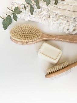 Cepillo corporal con mango de madera, piedra pómez, toalla blanca y un trozo de jabón sobre un fondo blanco. vista superior.