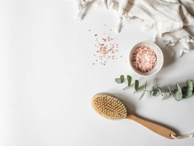 Cepillo corporal con mango de madera, toalla blanca y cuenco con sal marina rosa