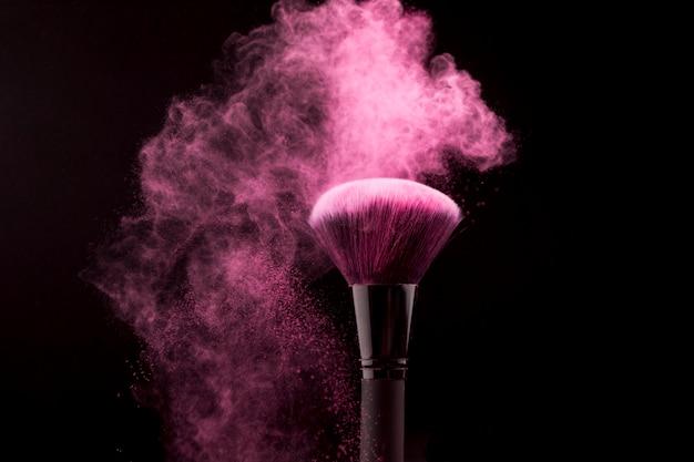 Cepillo cosmético en nube de polvo rosado sobre fondo oscuro