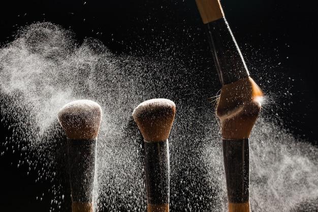 Cepillo cosmético con polvo cosmético que se extiende sobre fondo negro