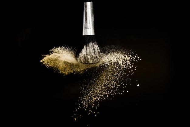 Cepillo cosmético con polvo de oro en polvo para untar
