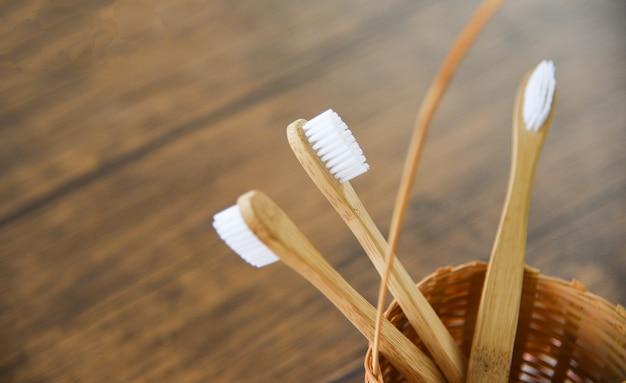 Cepillo de dientes de bambú en artículos ecológicos de plástico ecológico en fondo rústico