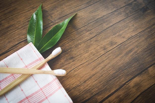 Cepillo de dientes de bambú y hoja verde sobre madera rústica.