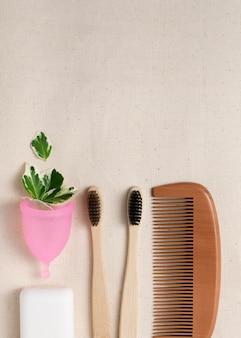 Cepillo de dientes de bambú, peine de madera, copa menstrual, vista superior de jabón con espacio de copia. cero desperdicio y concepto de reciclaje. artículos de higiene personal y salud.