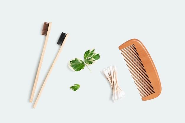 Cepillo de dientes de bambú, peine de madera, orejeras en una vista superior de fondo claro. cero desperdicio y concepto de reciclaje.