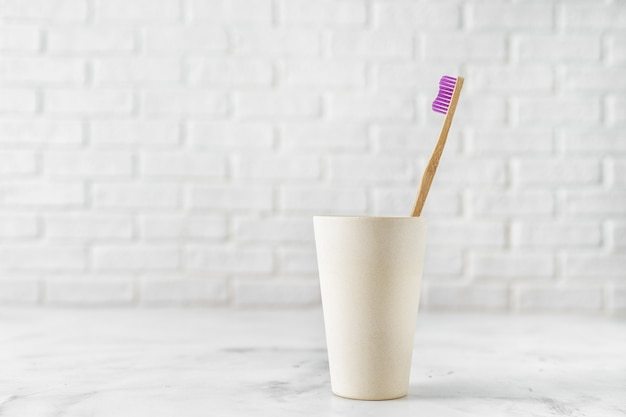 Cepillo de dientes de bambú en el soporte en blanco.