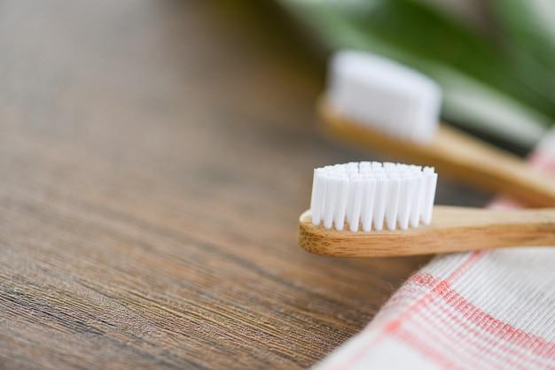 Cepillo de dientes de bambú en la tela ecológica, artículos libres de plástico natural y hoja verde