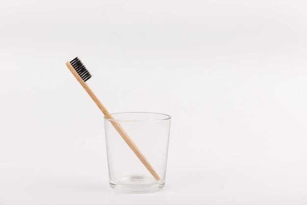 Cepillo de dientes de bambú en vidrio sobre fondo blanco. respetuoso del medio ambiente, sin plástico, cero vida útil