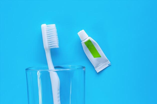 Cepillo de dientes blanco en el vidrio transparente con crema dental utilizada para limpiar los dientes sobre fondo azul