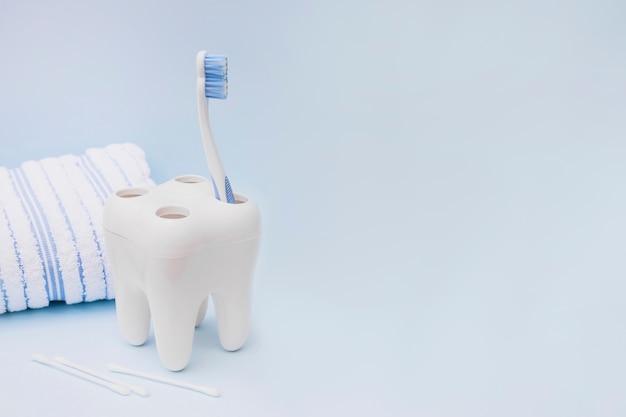 Cepillo de dientes; hisopo de algodón y una toalla sobre fondo azul