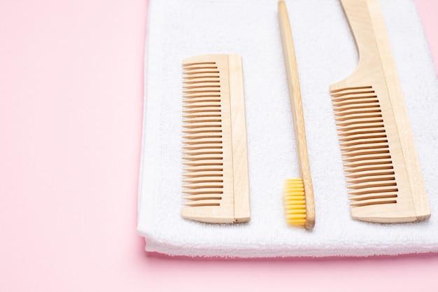 Cepillo de dientes de madera ecológica, peine y toalla de baño blanca sobre rosa