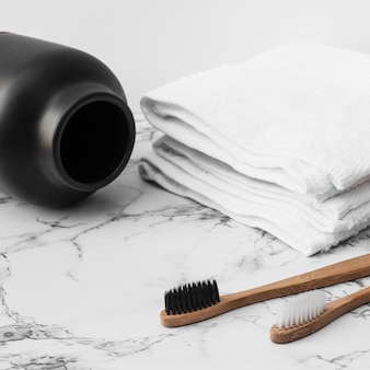 Cepillo de dientes de madera; toallas blancas y tarro sobre fondo de mármol