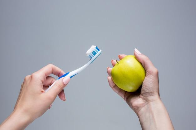 Cepillo de dientes y manzana en manos de mujer en gris