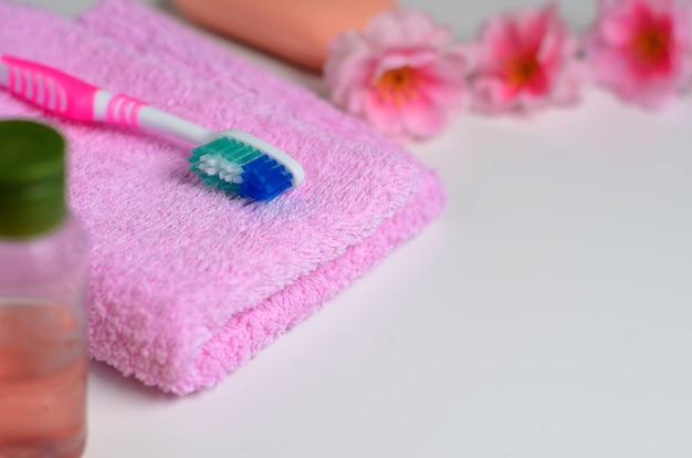 Cepillo de dientes rosa sobre una toalla rosa
