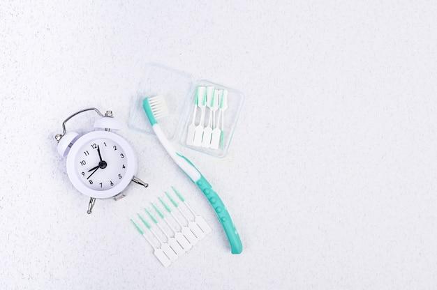 Cepillo de dientes sobre un fondo blanco y un reloj despertador. vista superior. lay flat