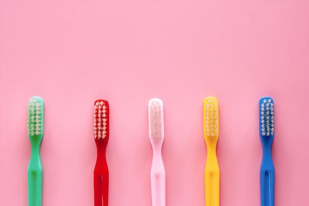 Cepillo de dientes utilizado para limpiar los dientes sobre fondo rosa