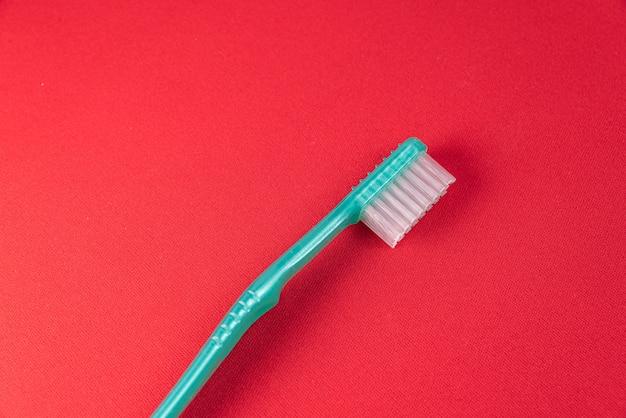 Cepillo de dientes verde sobre la mesa roja