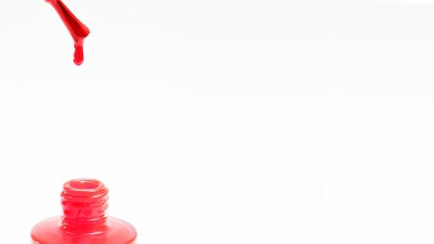 Cepillo de esmalte de uñas rojo con una gota cayendo en la botella sobre fondo blanco
