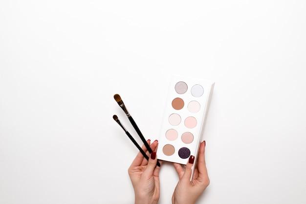 Cepillo de la explotación agrícola de la mujer joven con la pintura del color en blanco