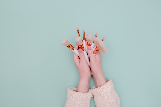 Cepillo de maquillaje profesional cosmético en esteticista de mano femenina sobre fondo neo mint. vista horizontal superior copyspace